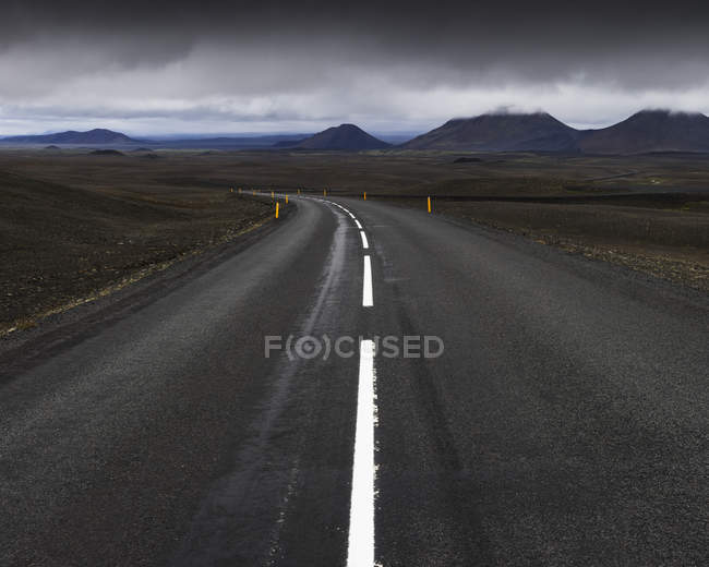 Road and mountain range under cloudy sky — Stock Photo