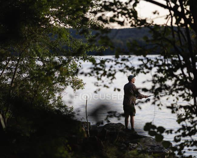 Man fishing in lake at sunset, selective focus — Stock Photo