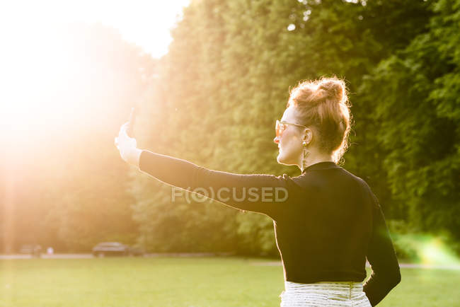 Woman photographing in park, selective focus — Stock Photo