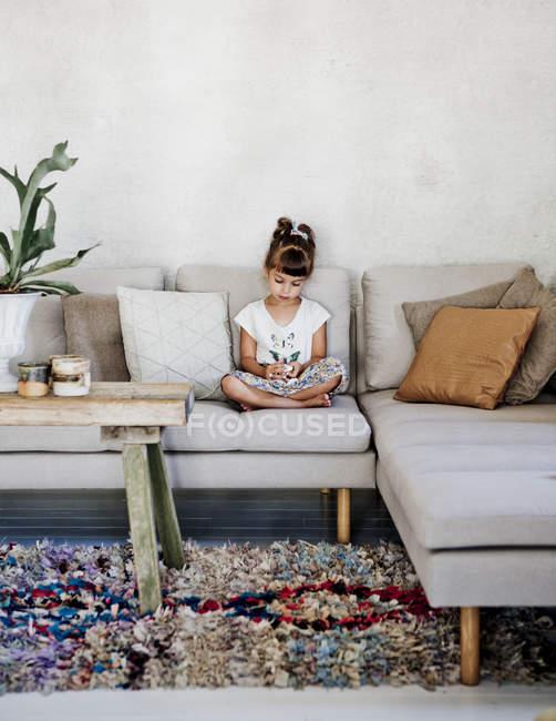 Mädchen schaut nach unten und sitzt auf Sofa — Stockfoto