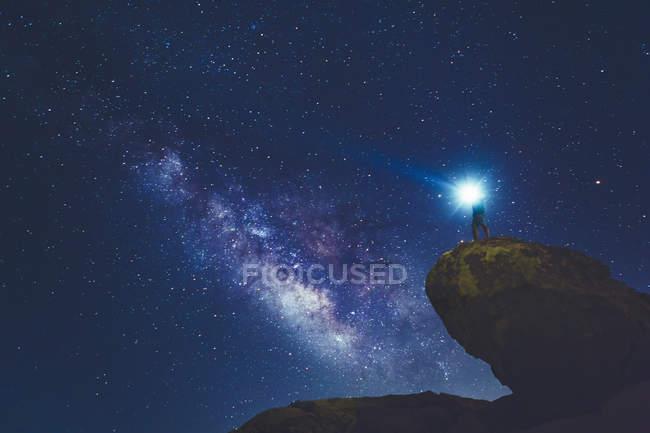 Hombre parado en la roca en el Parque Nacional Joshua Tree y mirando la Vía Láctea - foto de stock