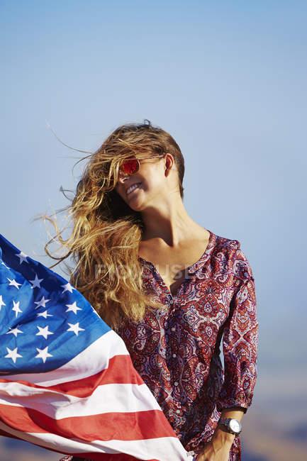 Молодая блондинка женщина, держа нас флаг на ветру — стоковое фото