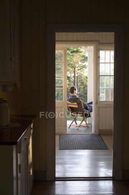 Homem maduro sentado no pátio em casa — Fotografia de Stock