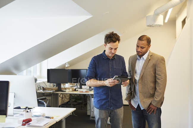 Businessmen standing side by side and looking on digital tablet in office — Stock Photo