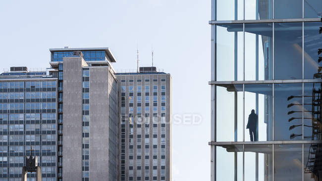 Person standing in front of windows in office building — Stock Photo