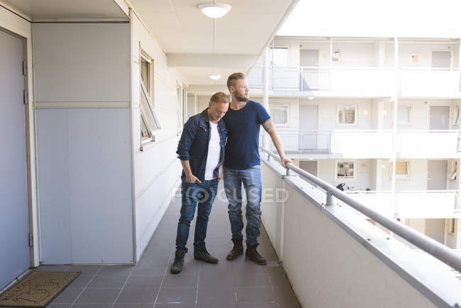Gay couple standing on balcony, focus on foreground — Stock Photo