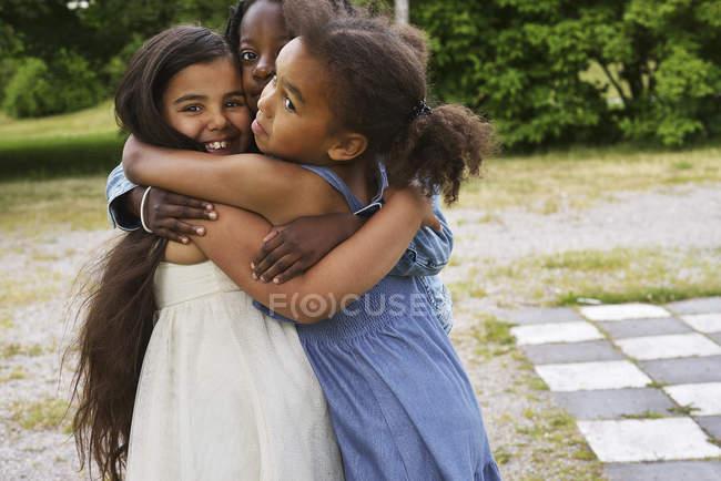 Porträt von drei Mädchen, die sich umarmen — Stockfoto