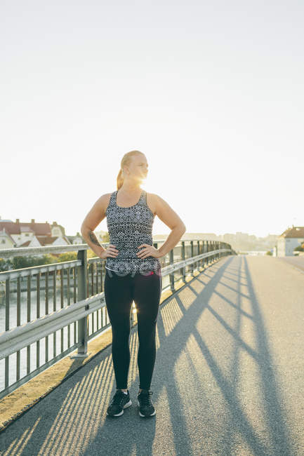 Young woman exercising on bridge in backlit — Stock Photo