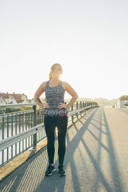Junge Frau, die Ausübung auf Brücke im Gegenlicht — Stockfoto
