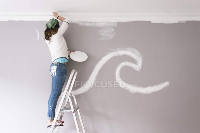 Woman standing on ladder and painting wall of home — Stock Photo