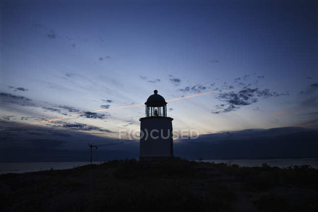 Lighthouse silhouetted at cloudy sunset sky — Stock Photo
