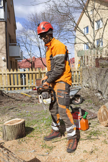 Arborist in protective workwear cutting log — Stock Photo