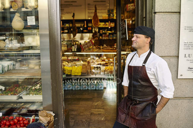 Man in apron standing in front of store — Stock Photo