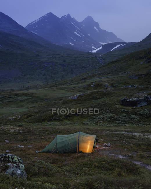 Illuminated tent by Jotunheimen range at dusk — Stock Photo