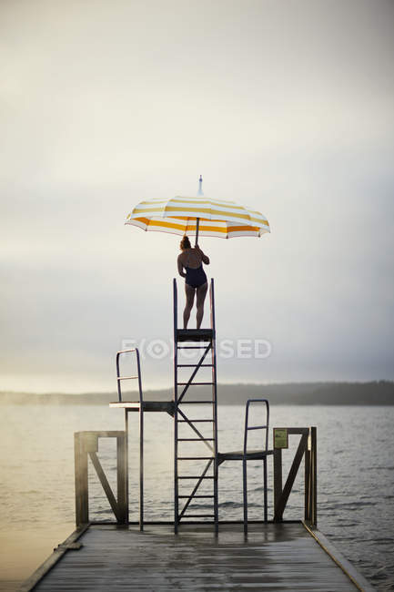 Woman with umbrella standing on ladder by lake — Stock Photo