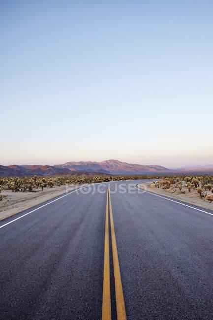 Порожній пустелі дорогу з гірського хребта в сутінках — стокове фото