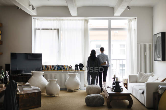 Couple looking through window in living room — Stock Photo