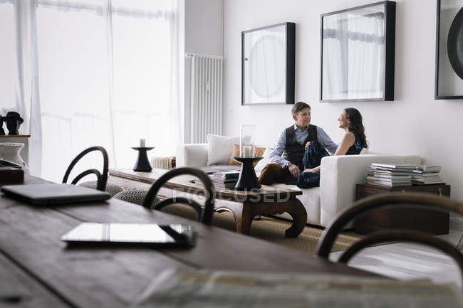 Пара, сидя на диване в гостиной, фокус на фоне — стоковое фото