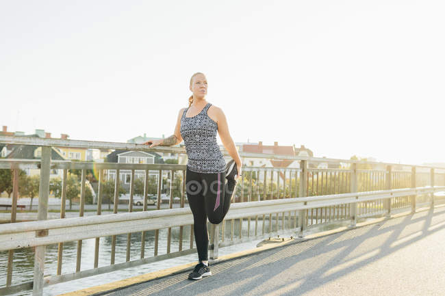 Young woman doing exercises on bridge — Stock Photo