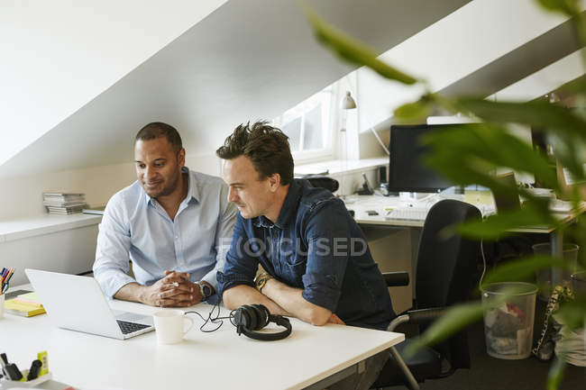 Businessmen sitting side by side and looking on laptop in office — Stock Photo
