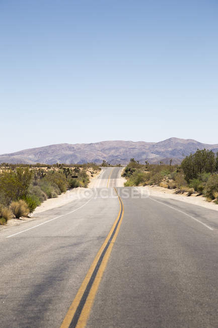 View along road leading through mountain valley — Stock Photo