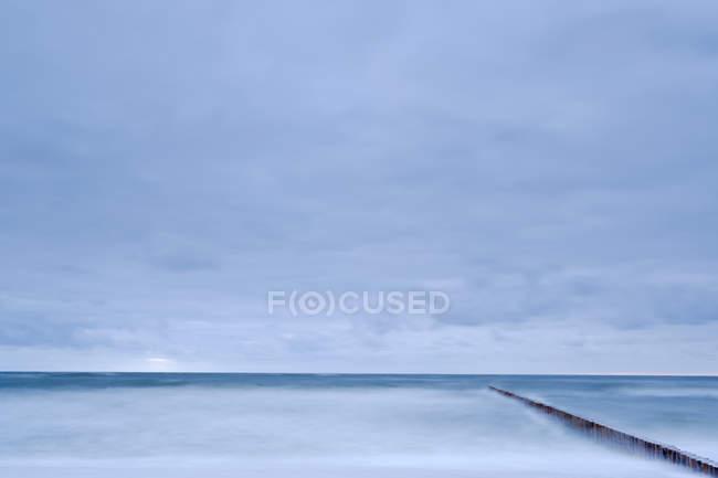 Tir longue exposition du paysage marin avec brise-lames sous ciel moody — Photo de stock