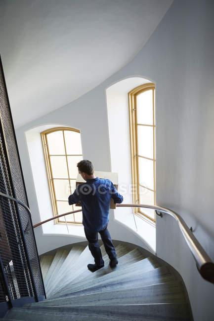 Vue grand angle de l'homme marchant sur des marches portant la boîte — Photo de stock