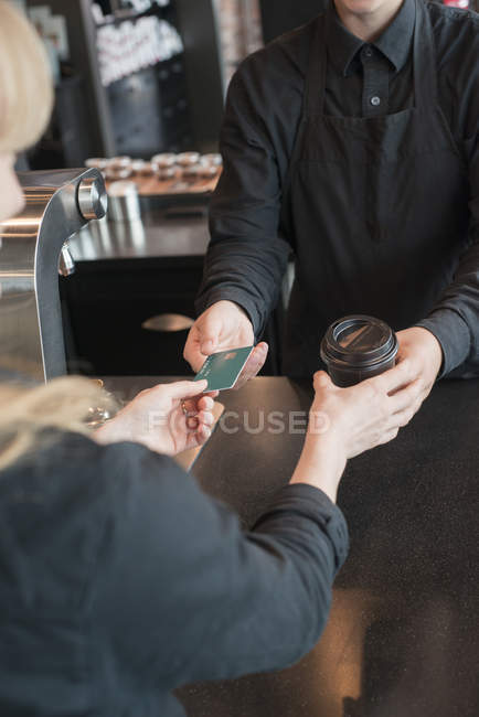 Young woman selling coffee at coffee shop — Stock Photo