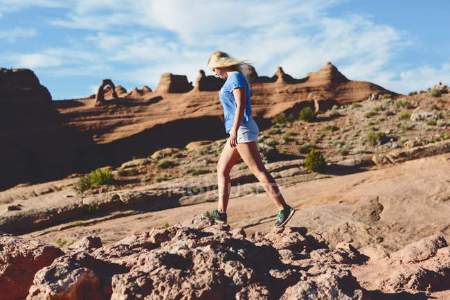 Side view of woman walking on rocks in Arches National Park — Photo de stock