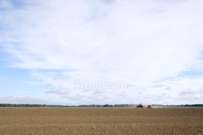 View of agricultural field with distant working tractor — Stock Photo