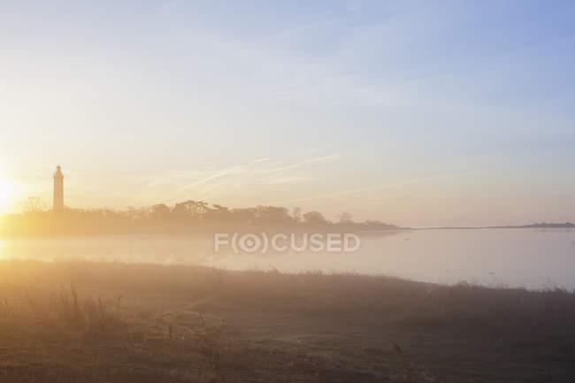 Берег моря с маяком на восходе солнца свет с голубым небом — стоковое фото
