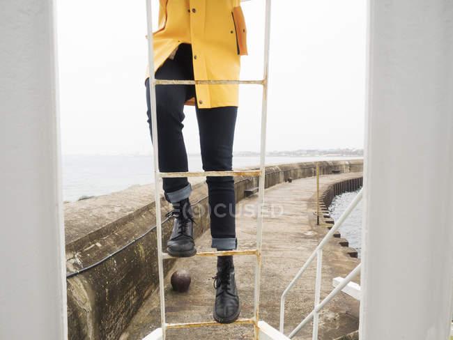Man wearing yellow raincoat climbing on ladder — Stock Photo