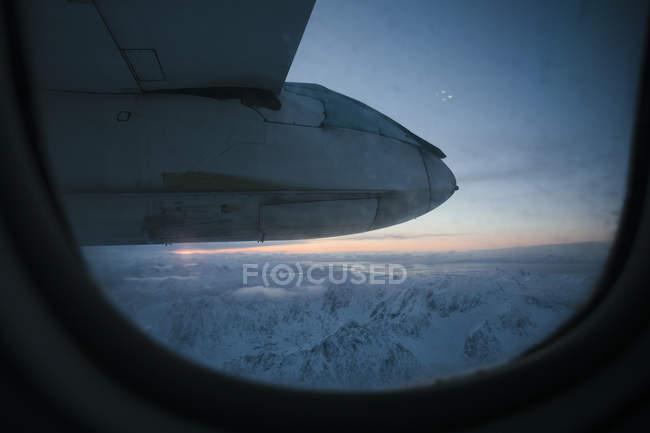 Vue par la fenêtre de l'avion, chaîne de montagnes en arrière-plan — Photo de stock