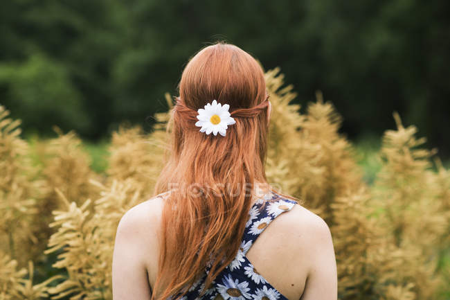 Young woman wearing floral dress and daisy flower in her hair — Stock Photo