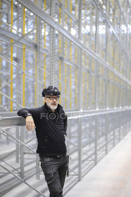 Homme debout devant la construction regardant la caméra — Photo de stock