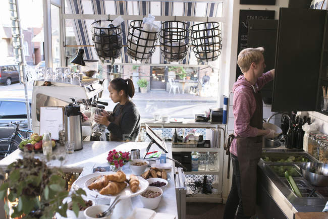Женщина и мужчина, работающих на коммерческих кухне, фокус на фоне — стоковое фото