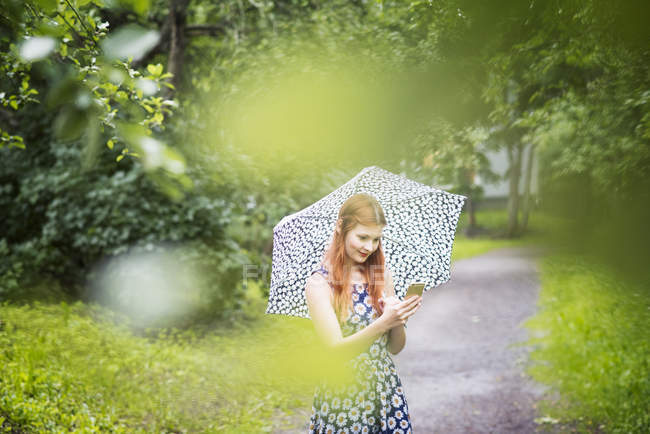 Woman in floral dress using smartphone while standing with umbrella in park — Stock Photo