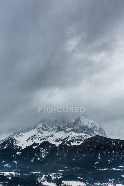View of snowcapped mountains under cloudy sky — Stock Photo