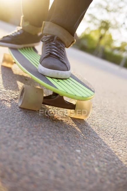 Pieds d'homme sur cruiser skateboard au soleil — Photo de stock