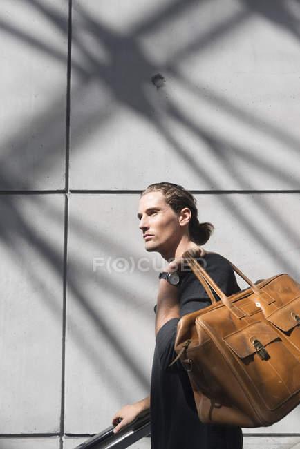Hombre joven marrón bolsa de luz del sol - foto de stock