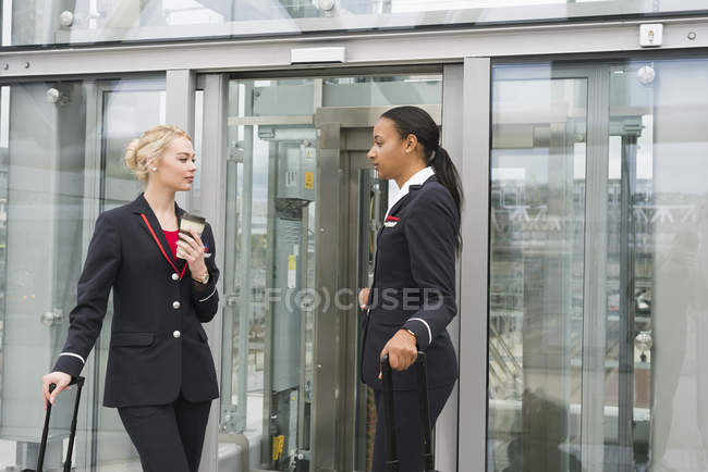 Stewardesses standing with suitcases against buildings exterior — Stock Photo