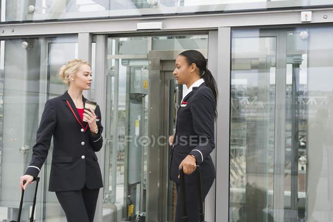 Стюардеси стоячи з валізами проти екстер'єру будівлі — стокове фото