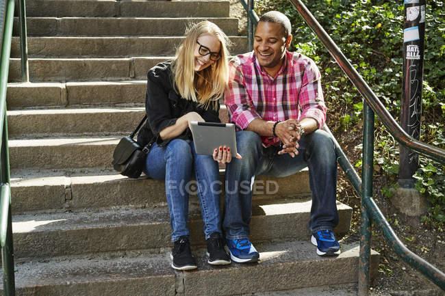 Чоловік і жінка сидять пліч-о-пліч на кроках і дивлячись на цифровий планшет — стокове фото