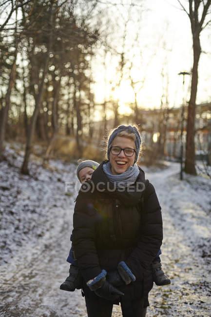 Risas media adulta mujer que lleva hijo - foto de stock
