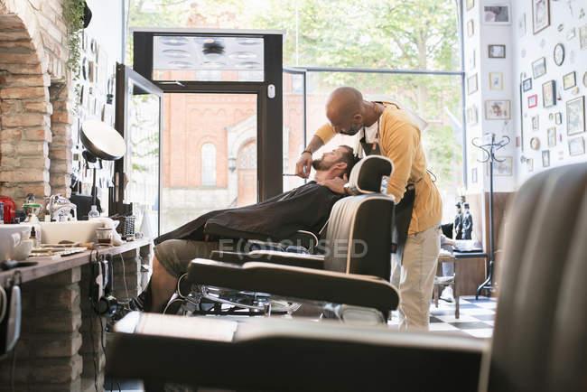 Парикмахерская для бритья клиент в парикмахерской, фокус на фоне — стоковое фото