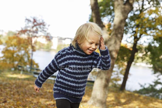 Блондинка хлопчик, сміючись в Осінній Парк — стокове фото