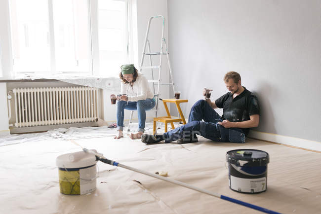 Couple using smartphones in room during renovation, — Stock Photo