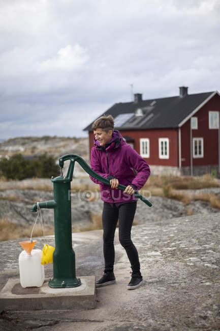 Femme d'âge mûr puits de pompage eau forme — Photo de stock