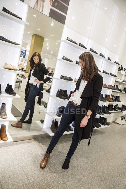 Woman choosing shoes in clothes store — Stock Photo
