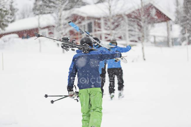 Мужчины с лыжами, ходьба вверх по склону на Borgafjall — стоковое фото
